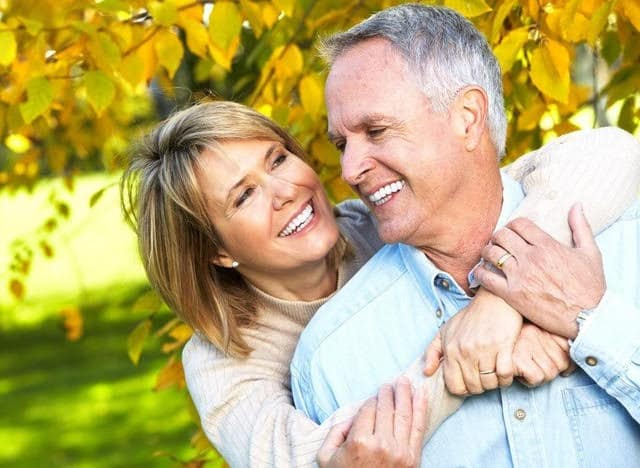 Smiling couple with new dentures